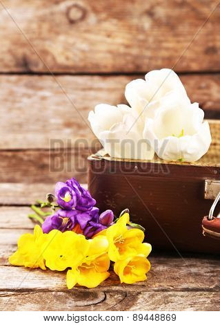Old wooden suitcase and flowers on wooden background