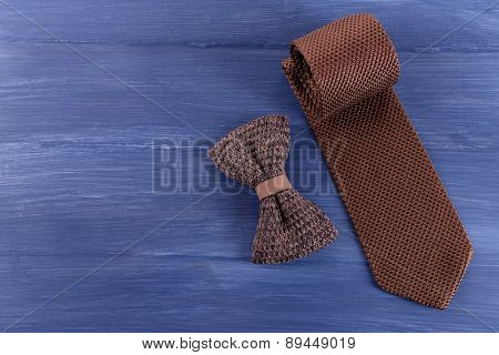 Male tie and bow tie on color wooden table background
