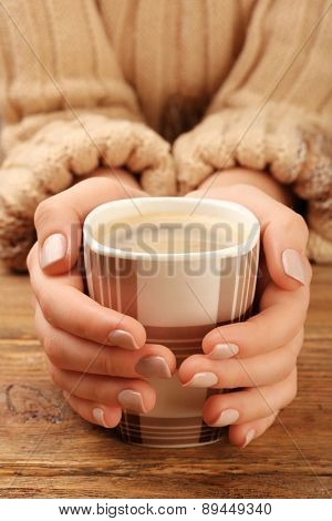 Female hands holding cup of coffee on wooden table closeup