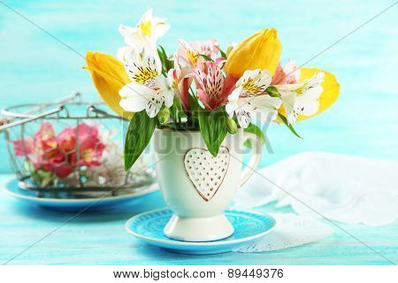 Beautiful flowers in cup, on color wooden background