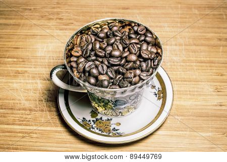 Cup With Roasted Coffee Beans On A Wooden Surface