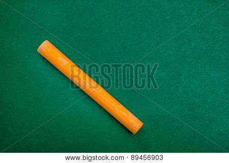 Single Orange Piece Of Chalk On Green