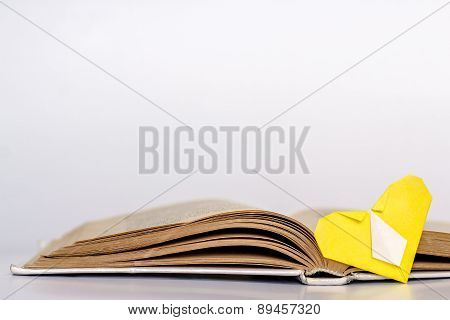 Open book and origami yellow heart with tie.