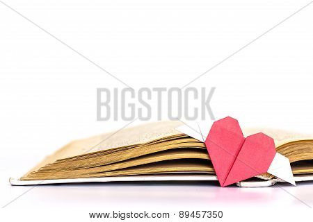 Open book with origami red heart isolated