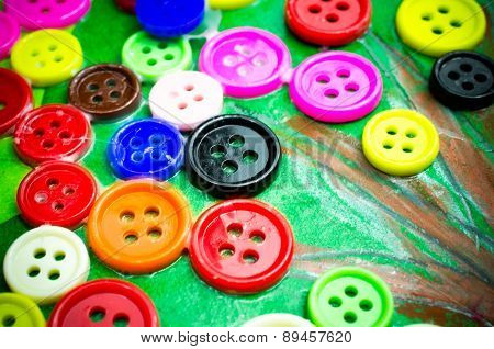buttons of many colors glued on paper