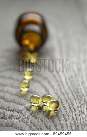 fish oil capsules with bottle on wooden table