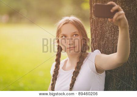 teenage girl taking selfie using mobile phone in park under the tree