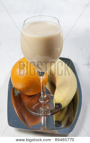 Smoothies Of Orange And Banana In A Glass On A    High Leg On A Metal Tray .