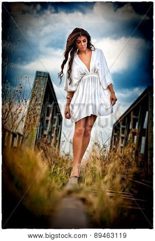 Sensual girl with white dress walking on the railway under the blue sky. Beautiful woman