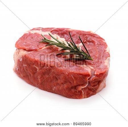 Raw Ribeye Steak Garnished With Sprig Of Rosemary
