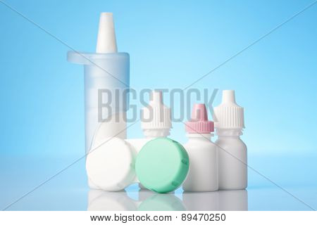 Disinfecting solution for contact lenses and eye drops on blue background