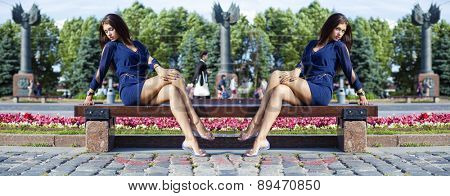Beautiful young woman sits on a bench in a summer park
