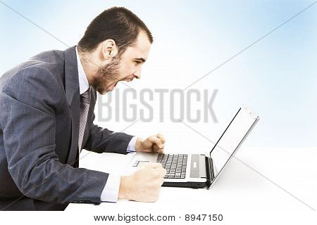 Businessman screaming against a laptop
