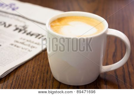 Coffee And Newspaper On Wood Table