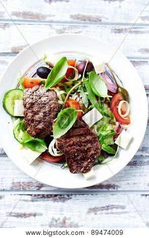 Grilled beef steaks with salad