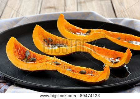 Cut Butternut Squash With Pumpkin Seeds On Black Tray