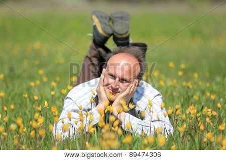 happy man on flower meadow in sunny day