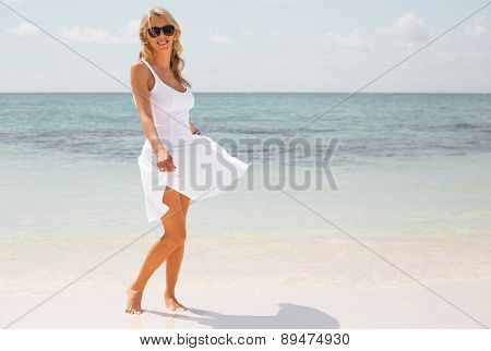 Happy woman in white dress enjoying vacation on tropical beach