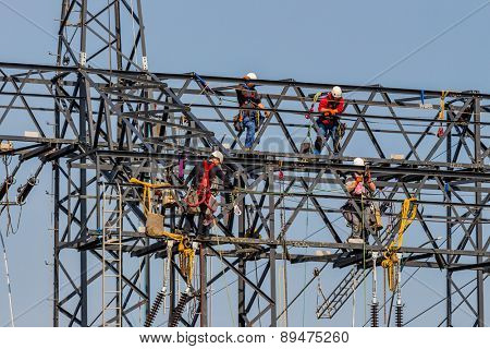 workers on electricity poles. a new power line will be built