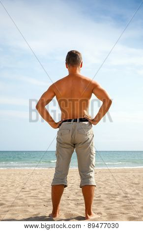 Young Man In Shorts Stands On The Sandy Beach