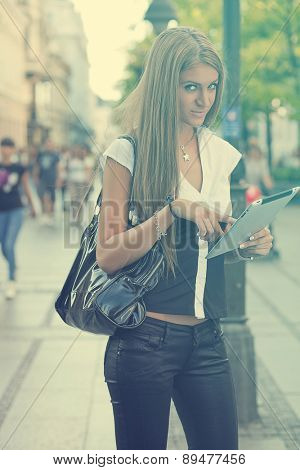 Young Beautiful Business Woman with tablet computer walking on urban street, downtown