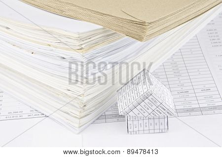 Brown Envelope And Overload Of Old Paperwork With House