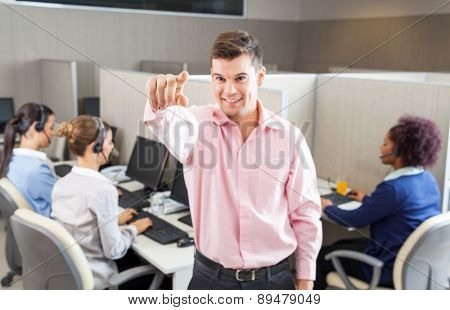 Young male customer service agent pointing while female colleagues working in background at call center
