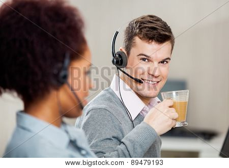 Portrait of smiling male customer service representative having tea in office