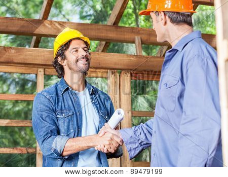 Male architects greeting each other in wooden cabin at construction site