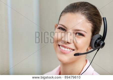 Closeup portrait of smiling female customer service representative wearing headset in call center