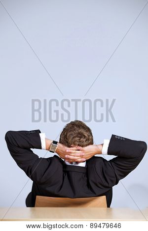 Rear view of businessman sitting in office with hands behind head