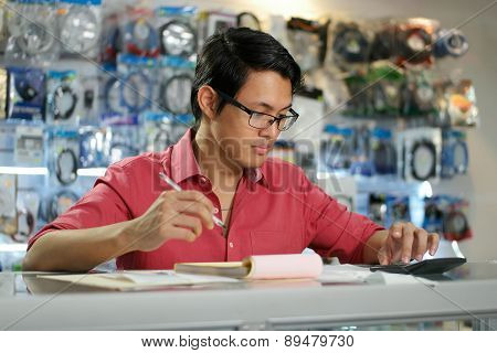 Chinese Man In Computer Shop Checking Bills And Invoices