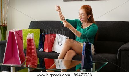 Latina Girl With Shopping Bags Tries Necklace On Sofa