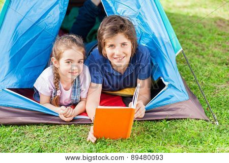 Portrait of smiling siblings reading book in tent at park