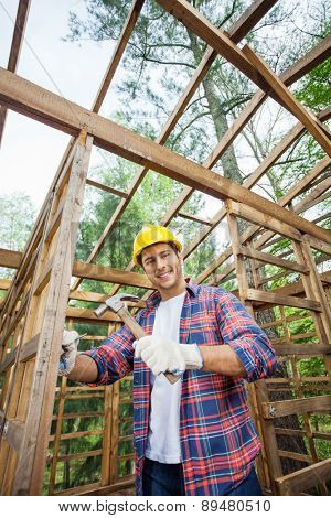 Portrait of smiling construction worker hammering in incomplete timber cabin at site