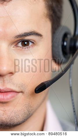 Closeup portrait of confident male customer service representative wearing headset in office