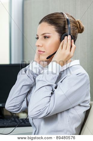 Young female service agent wearing headset and listening to customer carefully in office
