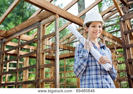 Portrait of beautiful female architect holding blueprint in incomplete wooden cabin at construction site