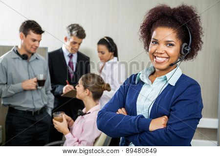 Portrait of happy female customer service representative standing arms crossed while team discussing in background at office