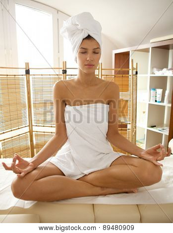 Young woman wrapped in towel doing yoga, eyes closed