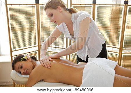 Young woman receiving massage from masseuse