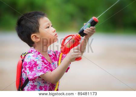 Boy play the gun in Songkran holiday