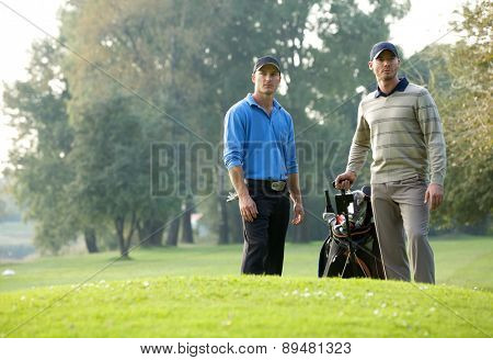 Young men standing with trolley in golf course
