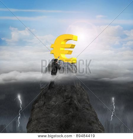 Businessman Hand Wanting Euro Symbol On Peak With Sunny Stormy