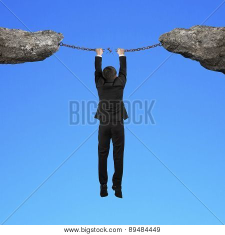 Businessman Hand Hanging The Cracking Iron Chains Connect Two Cliffs