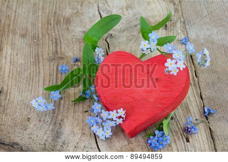 Red Wooden Heart Shape With Forgett-me-not Flowerd On Old Wood
