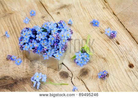 Forget-me-not Flowers In A Silver Heart Shape On Rustic Wood