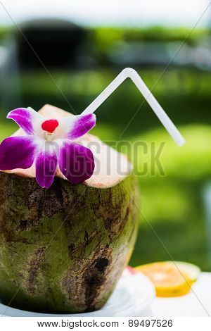 Coconut with straw and flower