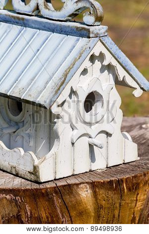 Wooden ornate birdhouse on tree stump