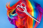 stock photo of wig  - scissors with color wig on a blue background - JPG